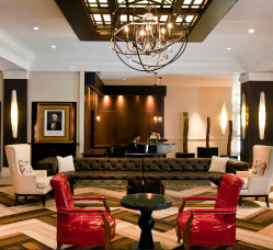 Inviting lobby at The Sam Houston hotel with red chairs and black accents